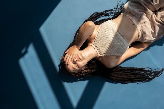 Chica de vista superior con rastas en el suelo