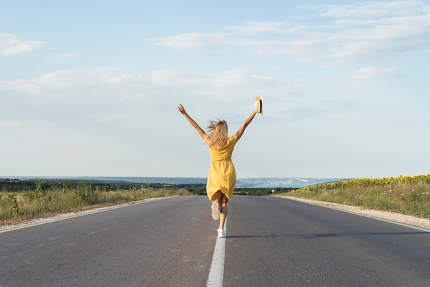 Chica de vista trasera corriendo en medio de la calle
