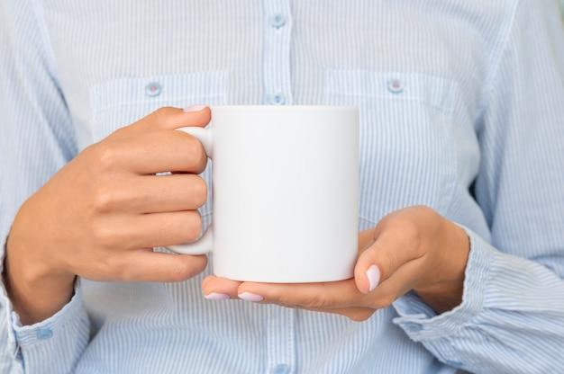Chica viste camisa azul sostiene una taza de cacao. espacio para su marca de texto.