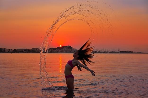 Chica volteando el pelo tirón en la playa de la puesta del sol