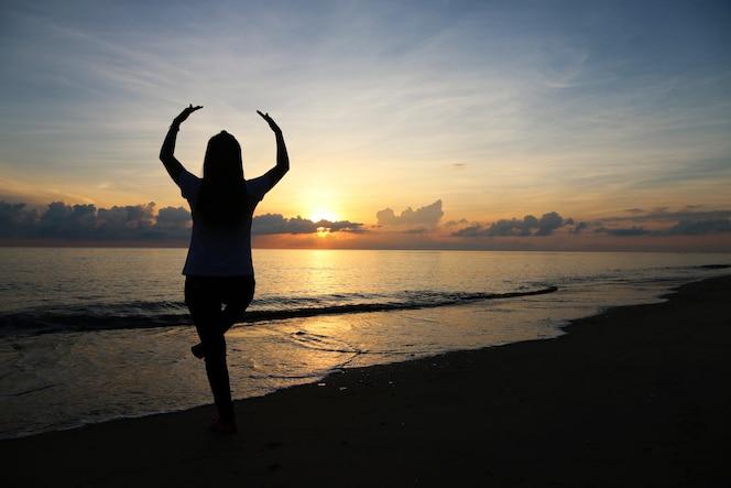 Chica yoga en la mañana de la playa
