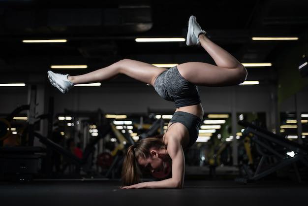 Chica yogui haciendo inversión avanzada y equilibrio de brazos escorpión parada de manos vrischikasana