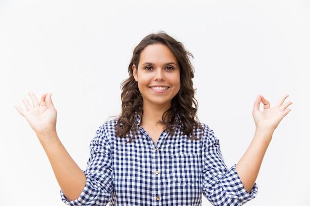 Chica yogui pacífica feliz haciendo gesto zen de mano