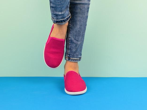 Chica en zapatillas rojas y pantalones rotos caminando sobre el piso azul.