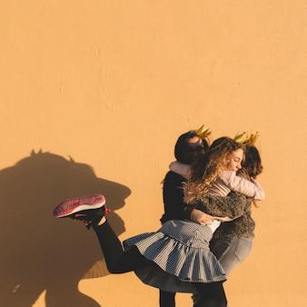 Chicas abrazándose cerca de la pared