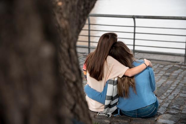 Chicas abrazándose enfrente de agua