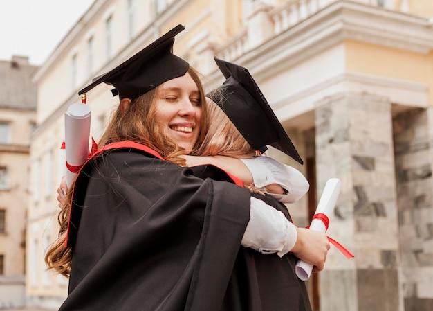 Chicas abrazándose en la graduación