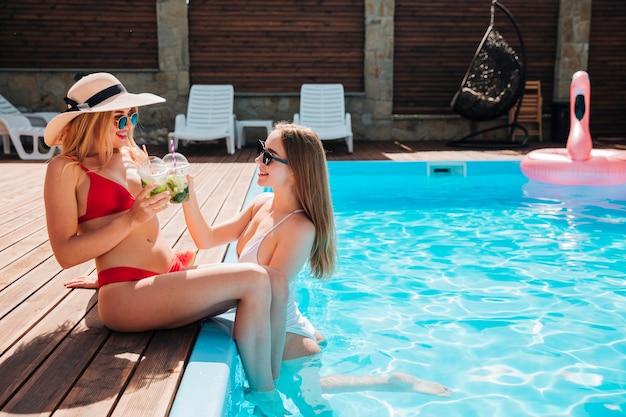 Chicas aclamando en el borde de la piscina.