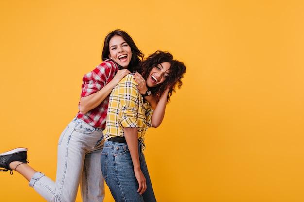 Chicas activas bailan en jeans y blusas de colores a cuadros. las novias se abrazan y se ríen sinceramente.