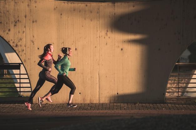 Chicas activas corriendo al atardecer