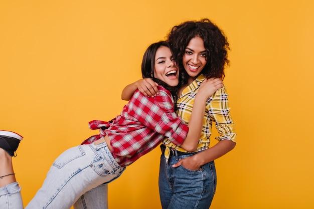 Las chicas activas están felices de conocerse. morena en camisa roja abraza a un amigo con el pelo rizado.