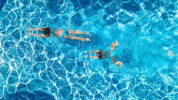 Chicas activas en vista de drone aéreo de agua de piscina
