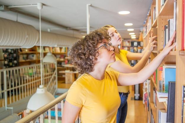 Chicas adolescentes buscando libro en biblioteca