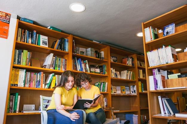 Chicas adolescentes leyendo en la acogedora biblioteca