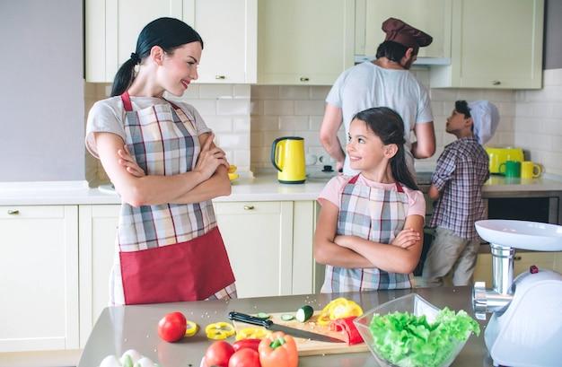 Las chicas agradables y positivas se paran una frente a la otra y sonríen. han cruzado las manos. los niños trabajan juntos detrás de las mujeres jóvenes. ellos cocinan.