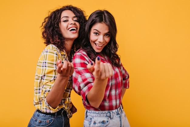 Las chicas alegres sugieren acercarse a ellas. retrato de alegres morenas sonrientes en traje elegante