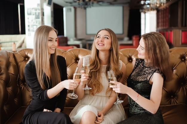 Chicas alegres tintineando copas de champán en la fiesta