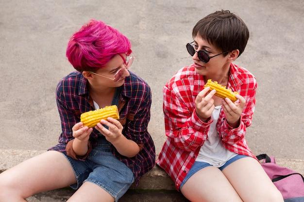 Chicas de alto ángulo comiendo maíz juntos