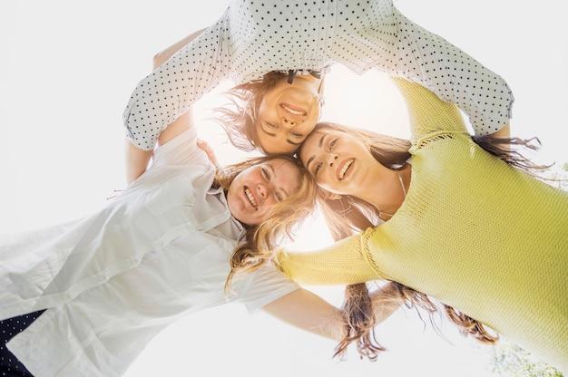 Chicas de ángulo bajo abrazándose y mirando hacia abajo