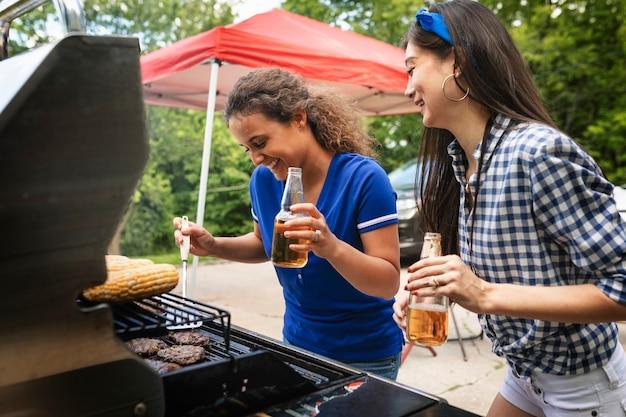 Chicas asando hamburguesas en una fiesta en la puerta trasera