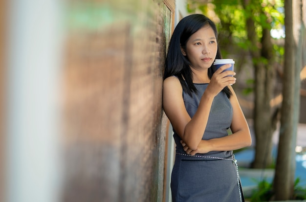 Chicas asiáticas beben café caliente en la cafetería