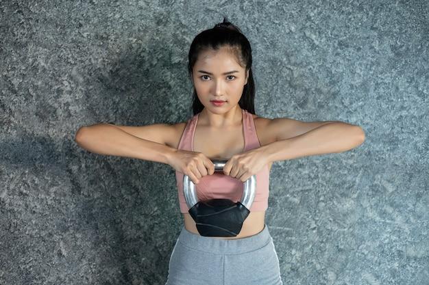 Las chicas asiáticas hacen ejercicio con el kettlebell en el gimnasio.