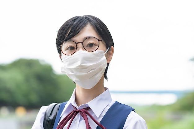 Chicas asiáticas de secundaria que van a la escuela con máscaras