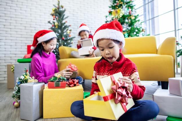 Chicas asiáticas sorprenden con un regalo y ayudan a decorar juntas para celebrar en el festival de navidad