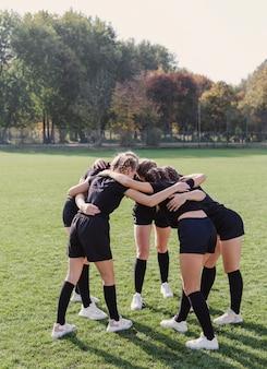 Chicas atléticas reunidas en círculo