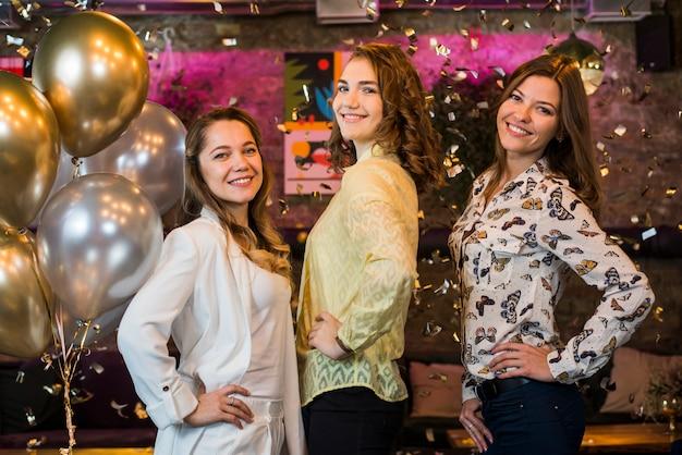 Chicas atractivas posando y sonriendo mientras disfrutan en la fiesta.