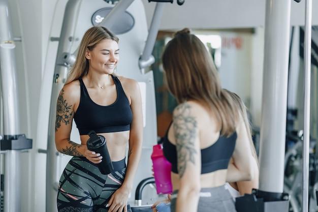 Chicas atractivas en ropa deportiva en el gimnasio se comunican. vida deportiva y ambiente de fitness.