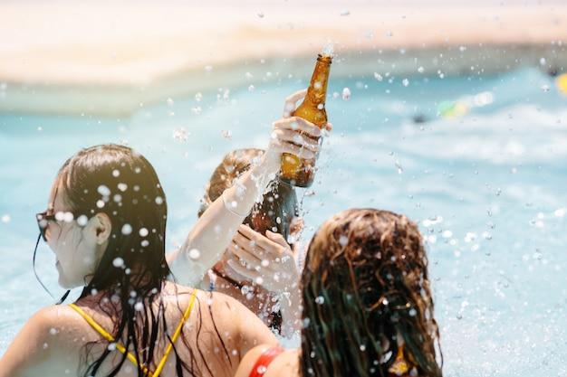 Chicas bailando dentro de una piscina con botellas de cerveza