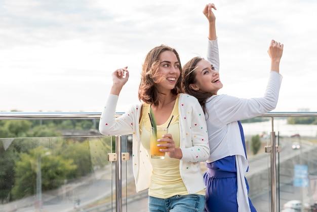 Chicas bailando espalda con espalda en una fiesta