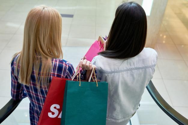 Chicas bajando las escaleras mecánicas en el centro comercial