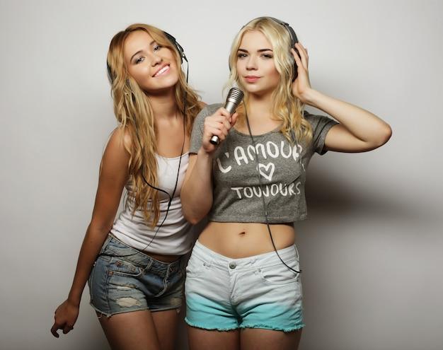 Chicas de belleza con un micrófono cantando y bailando