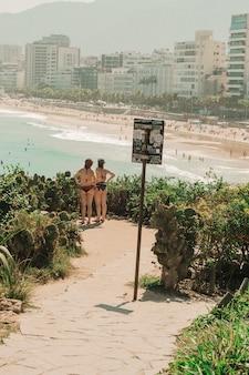 Chicas en bikini de pie y mirando a la playa en río de janeiro.
