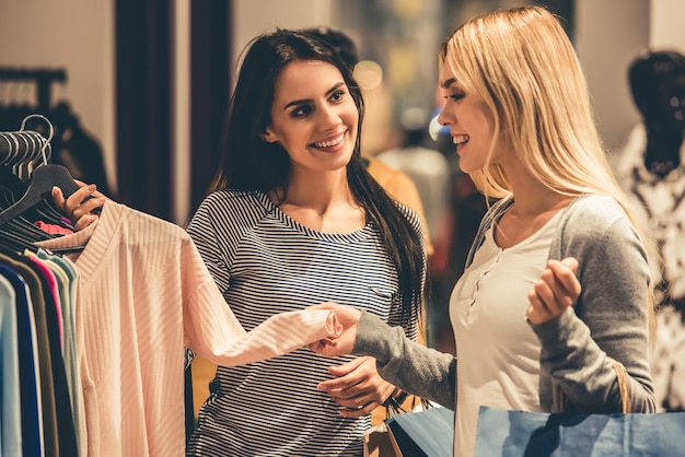 Las chicas con bolsas de compras eligen la ropa