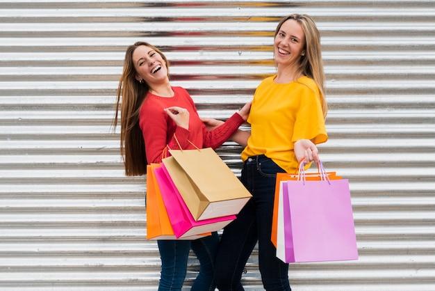 Chicas con bolsas de compras mirando a la cámara