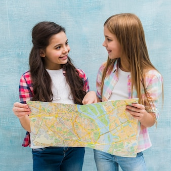 Chicas bonitas sosteniendo un mapa en la mano mirando el uno al otro