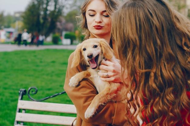 Las chicas caminan en el parque con perro.