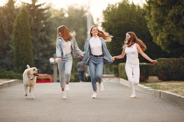 Chicas caminando en una ciudad de primavera con lindo perro