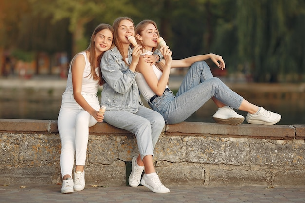 Chicas caminando en una ciudad de primavera y tienen helado en la mano
