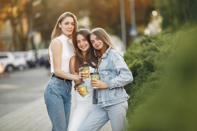 Chicas caminando en una ciudad de primavera y tomando café
