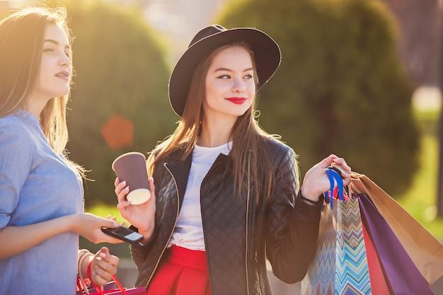 Chicas caminando con compras en calles de la ciudad