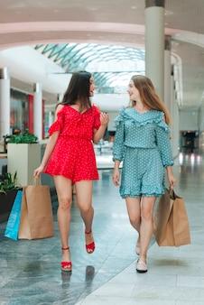 Chicas caminando con sus maletas en el centro comercial.