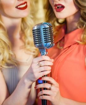 Las chicas cantan karaoke en el restaurante.