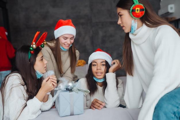 Chicas chismeando en casa en la víspera de año nuevo. divirtiéndose en la celebración de la fiesta, bebiendo champán