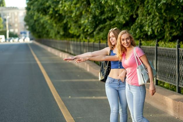 Chicas cogiendo un coche en la ciudad.