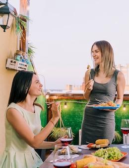 Chicas comiendo aperitivos en la fiesta en la azotea