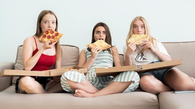 Chicas comiendo pizza y viendo una película de terror.